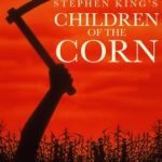 Children of the Corn Movie Cover. Red sky silhoutte of child's hand with hatchet over a corn field
