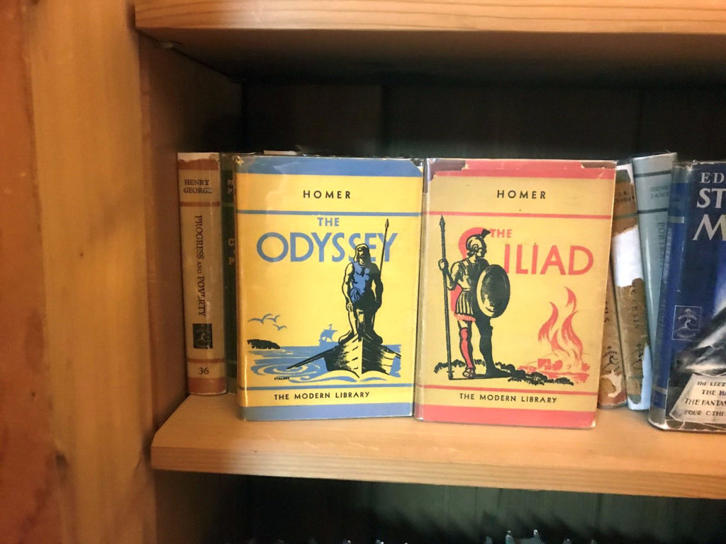 Two similar designs for two books both have a soldier standing strong in black printed ink. Shadows are in another color, blue for the Odyssey and red for Iliad.